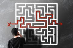 Man looking at chalk drawing of maze labyrinth on blackboard. Rear view of man looking at chalk drawing of maze labyrinth on blackboard royalty free stock photo