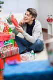 Man Looking At Christmas Gift In House Stock Images