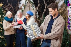 Man Looking At Christmas Present With Family In Royalty Free Stock Image
