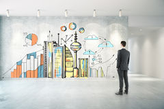 Man looking at city sketch. Thoughtful businessman in concrete room looking at wall with creative city sketch with business charts. Industry concept Stock Photography