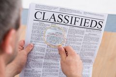Man looking classifieds through magnifying glass Royalty Free Stock Photos