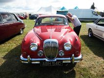 A man looking closely inside of vintage red Jaguar Mark1 car. Displayed outdoor at Northumberland Wings & Wheels festival at Eshott Airfield north of Morpeth stock photos