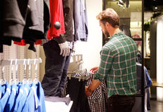 Man looking at clothes in a store. Portrait of a man looking at clothes in a store Stock Photos