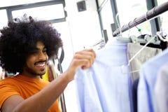 Man looking at clothes at store. Man smiling and looking at clothes at store Royalty Free Stock Photos