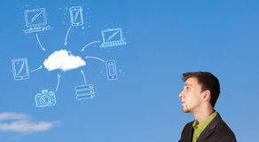 Man looking at cloud computing concept on blue sky Stock Image