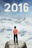 Man looking at cloud shaped numbers 2016 Stock Images