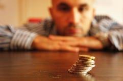 Man looking at coins Stock Image