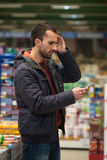 Man Looking Confused At Mobile Phone In Supermarket Royalty Free Stock Photography