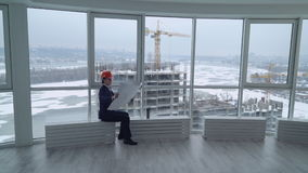 Man looking on the construction site through the window. stock footage