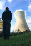 Man looking at cooling tower. A view of a man looking towards a huge cooling tower of a power generating plant Royalty Free Stock Photography