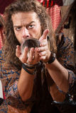 Man Looking into Crystal Ball. Serious Gypsy man coddling a crystal ball Stock Photography
