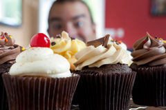 Man Looking at Cupcakes Stock Images