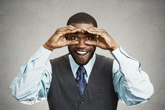 Man, looking curious, surprised, shocked through fingers like bi Royalty Free Stock Images