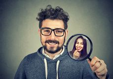 Man looking for date candidate with lens. Handsome bearded men holding magnifying glass inspecting young girl for girlfriend candidate stock photo