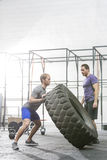 Man looking at dedicated friend flipping tire in crossfit gym Royalty Free Stock Photos