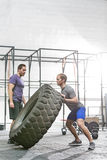 Man looking at dedicated friend flipping tire in crossfit gym Royalty Free Stock Photo