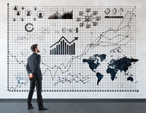 Man looking at diagrams. Back view of young businessman looking at business charts and diagrams in concrete interior. Finance concept stock photos