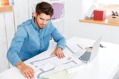 Man looking at diagrams on the table Stock Photo