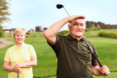 Man looking into the distance on course. Into distance. Senior men standing on course near his wife holding his hand near his forehead and looking into the Stock Images