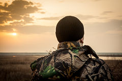 Man  looking into the distance. Man wearing in camouflage jacket standing on field during sunset and  looking into the distance Stock Photo