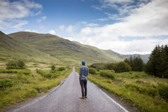 Man looking down a country road Royalty Free Stock Photo