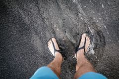 Man looking down at feet and sandals on volcanic black sand beac. Life balance concept. Man looking down at feet and sandals on volcanic black sand beach. Legs Royalty Free Stock Image