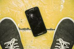 Man looking down between his shoes on floor his scratched and broken screen mobile phone after falling on the ground. Man looking down between his shoes on the Royalty Free Stock Photos