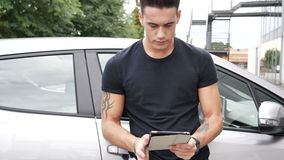 Man looking down at a tablet computer, outdoor. Handsome trendy man wearing black t-shirt leaning against car, looking down at a tablet computer that he is stock video
