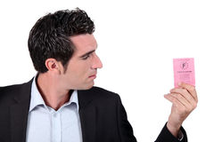 Man looking at driving licence Stock Images