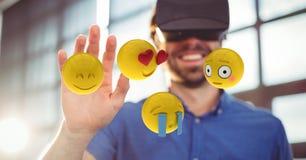 Man looking at emojis through VR glasses Stock Photos