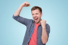 Man looking so excited putting his fist up. Young european man wearing a casual clothes, looking so excited putting his fist up, standing on a blue background royalty free stock photo