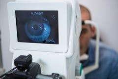 Man looking at eye test machine Stock Images