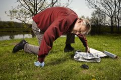Man found falled meteorite on outdoor location. Man looking for falling meteorite made happy find on spring meadow Royalty Free Stock Photography