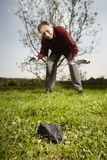 Man found falled meteorite on outdoor location. Man looking for falling meteorite made happy find on spring meadow Royalty Free Stock Photo