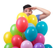 Man is looking far from behind a baloons bunch Stock Photo