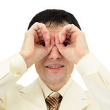 Man looking through fingers like binoculars Stock Images