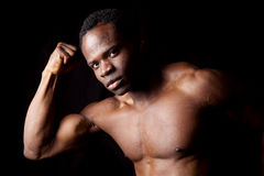 Man looking flexing. A man on a black background looking at the camera showing off his muscles Stock Images