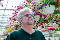 Man looking for flowering baskets Stock Photos