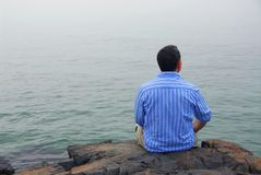 Man looking at fog. Man looking at the foggy ocean. Uncertain future concept Royalty Free Stock Photography