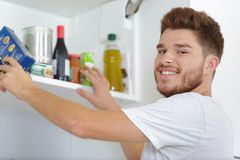 Man looking for food in cupboard royalty free stock photo