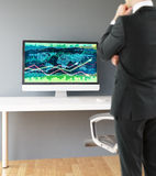 Man looking at forex chart. Thoughtful businessman looking at workplace with forex chart on computer monitor. Swivel-chair and wooden floor on concrete wall Royalty Free Stock Photo