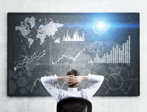 Man looking at forex graphs Stock Photos