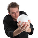 Man looking into a glass ball. Man looking up into a glass ball predicting the future, wearing a black coat. White background stock photos