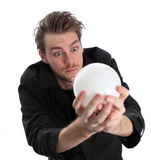 Man looking into a glass ball. Wearing a black jacket. White background stock photos