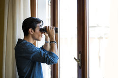Man looking through a glass door with binoculars Royalty Free Stock Image