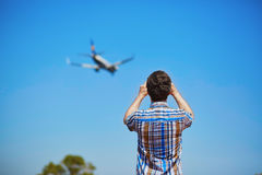 Man is looking at the glide path and landing plane. Or taking a photo of it. Aircraft spotting concept Stock Photography