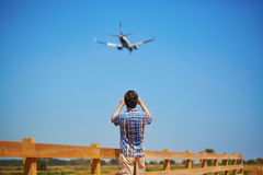 Man is looking at the glide path and landing plane. Or taking a photo of it. Aircraft spotting concept Stock Images