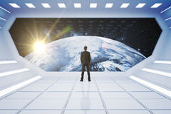 Man looking at globe. Back view of man in spaceship looking at globe. Elements of this image furnished by NASA. 3D Rendering Stock Image