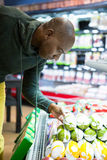 Man looking at goods in grocery section while shopping. In supermarket Royalty Free Stock Image