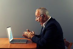 Man looking at graph and rejoicing. Excited senior man looking at graph and rejoicing Royalty Free Stock Photography